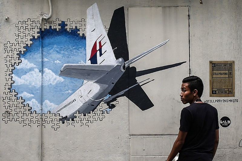 A file picture dated 06 March 2015 shows a man in front of a Malaysia Airlines flight MH370 mural painting at Shah Alam, outside Kuala Lumpur, Malaysia. (EPA Photo)