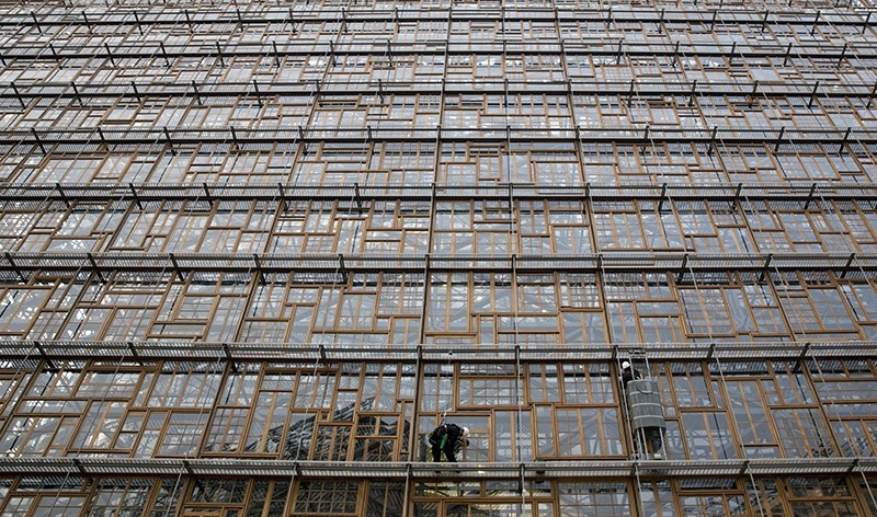 Window washers work at the new European Council building, Europa, in the European Quarter of Brussels on Thursday, Nov. 24, 2016. (AP Photo)