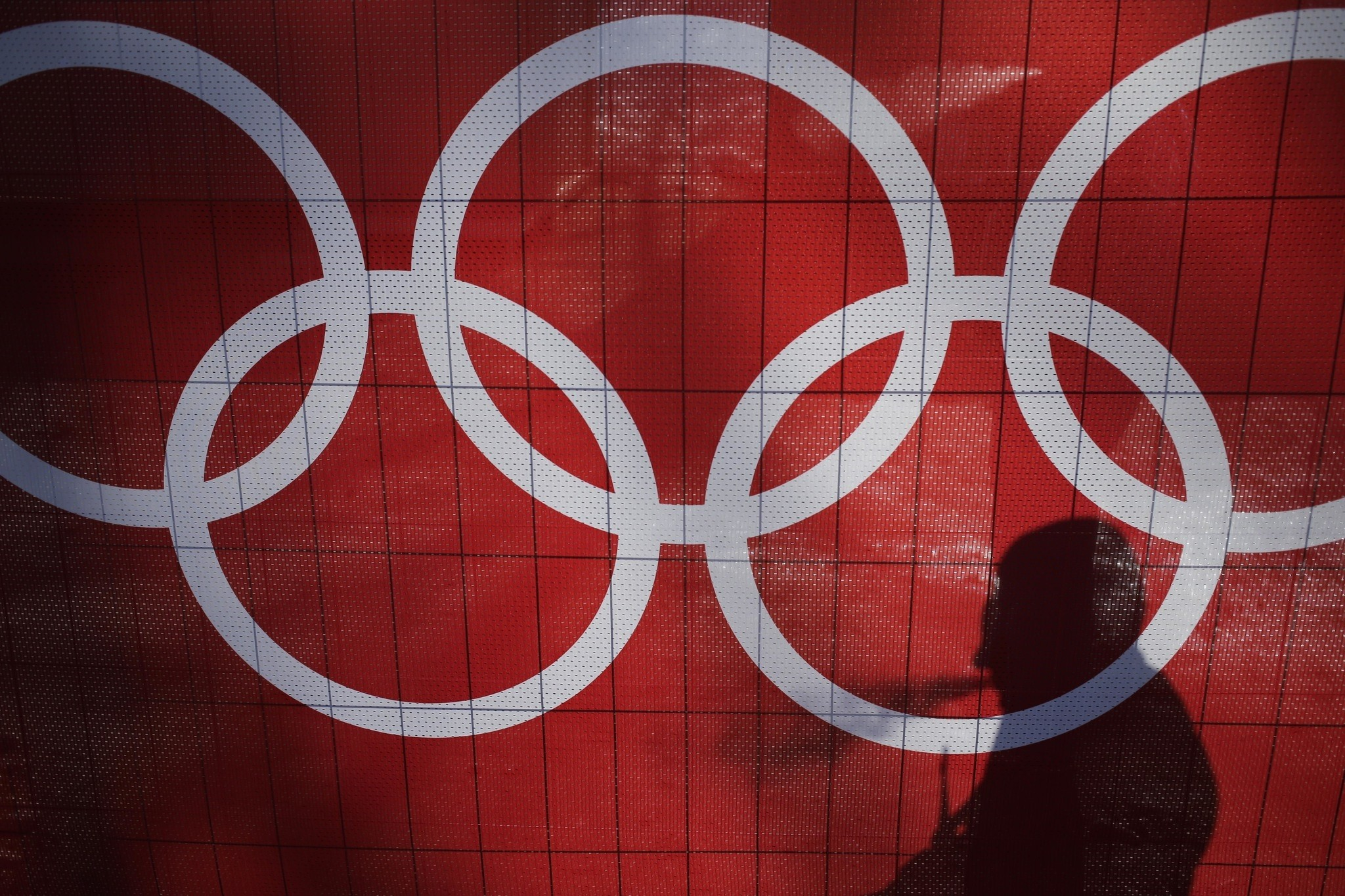 In this Feb. 15, 2014 file photo the shadow of a man is cast on the Olympic rings as he smokes at the Rosa Khutor Alpine Center, at the 2014 Winter Olympics in Krasnaya Polyana, Russia. (AP Photo)