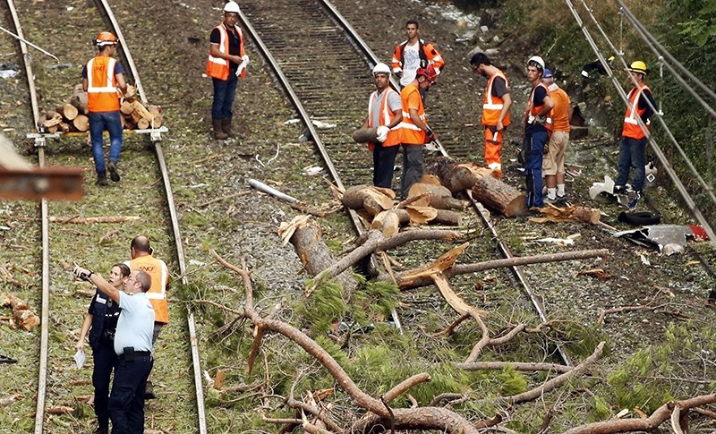 Railroad workers and French police officers clean the rails near Saint-Aunes in the South of France, 17 August 2016 (EPA Photo)