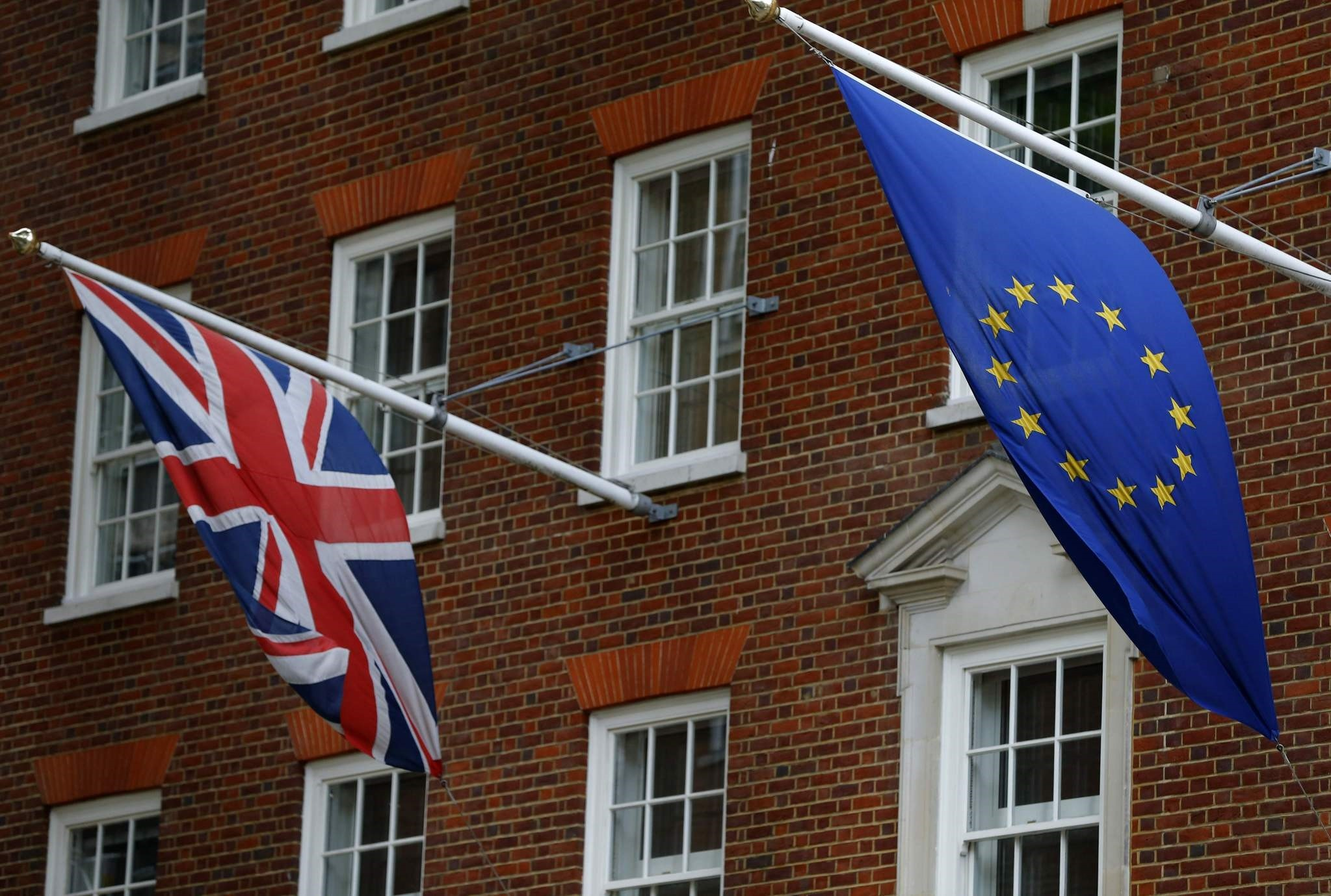 A Union flag (L), and a European Union (EU) flag fly above Europe House, the head office of the UK Representation of the European Commission, and the UK Information Office of the European Parliament. (AFP Photo)