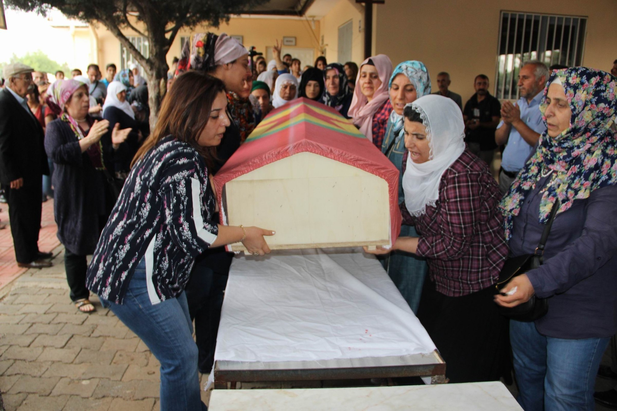 The co-mayor of Kayapu0131nar municipality in Diyarbaku0131r, Fatma Aru015fimet, is seen on the left carrying the coffin draped in a PKK flag.