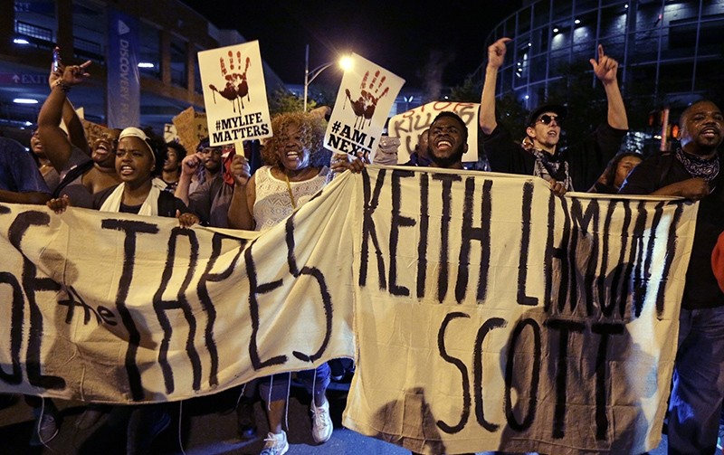 In this Friday, Sept. 23, 2016 file photo, protesters shout as they march in the streets of Charlotte, N.C., to protest the fatal police shooting of Keith Lamont Scott (AP Photo)