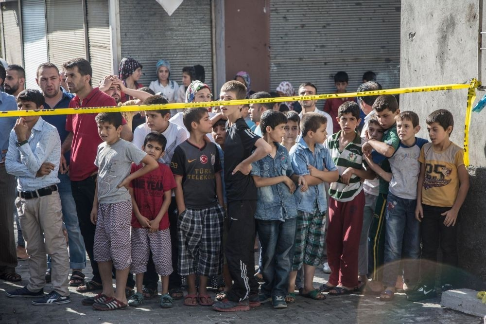 People standing near the explosion scene following the latest attack on a wedding ceremony that left 51 dead and 69 wounded in southeastern Gaziantep province near Turkey's border with Syrian on Aug. 21.