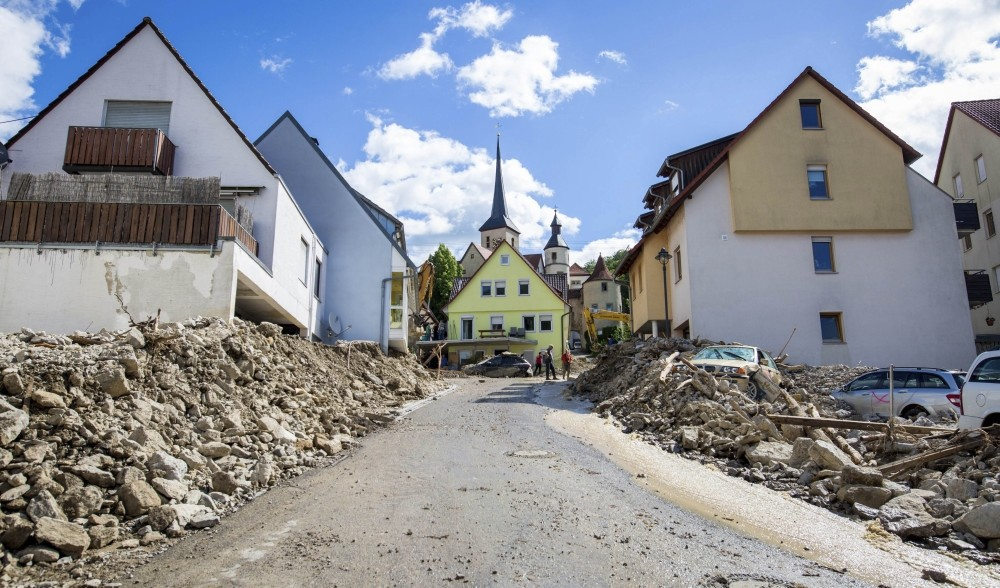 Dust coats the streets of Braunsbach and billows up as trucks bring in tar to fill the giant holes left from the devastating floods that hit the southern German village unexpectedly last month.