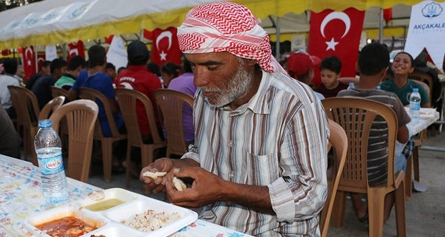 A Syrian man breaks his fast at an iftar dinner in last year's Ramadan hosted by Aku00e7akale Municipality (AA Photo)