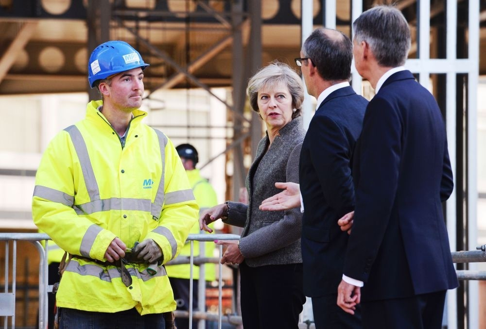 British Prime Minister Theresa May (2L) and British Chancellor of the Exchequer Philip Hammond (R) visit a construction site where new HSBC offices are being built in Birmingham Monday.
