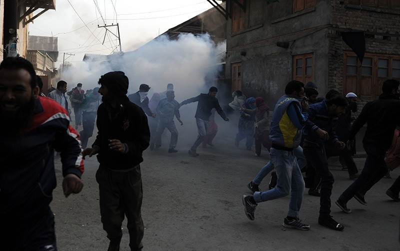 Kashmiri protesters run after Indian police fired teargas shells and pellets during the funeral procession for Qaiser Hamid, 16, killed by Indian forces in Srinagar on Nov. 5, 2016. (AFP Photo)