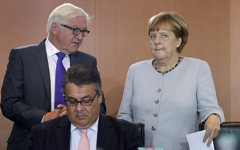 In this Aug. 31, 2016 file photo German Chancellor Angela Merkel, right, holds files as she talks to German Foreign Minister Frank-Walter Steinmeier (AP Photo)