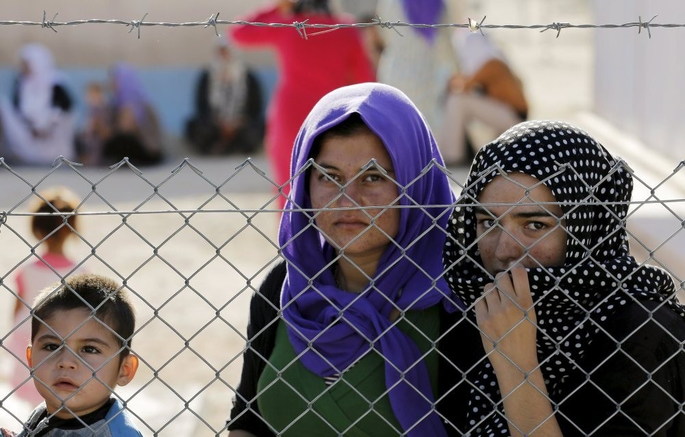 Refugees stand behind fences at a Syrian and Iraqi refugee camp in the southern Turkish town of Midyat in Mardin province, June 20, 2015.
