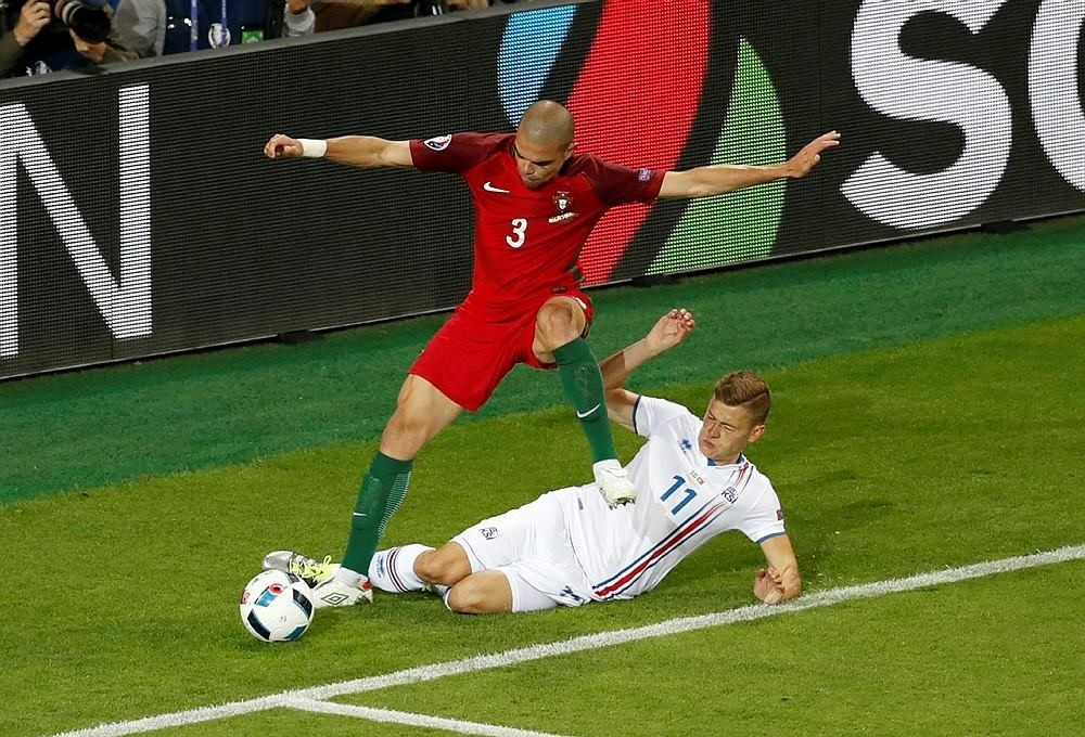 Portugal's Pepe, top, fights for the ball with Iceland's Alfred Finnbogason during the Euro 2016 Group F soccer match between Portugal and Iceland at the Geoffroy Guichard stadium in Saint-Etienne, France, Tuesday, June 14, 2016. (AP Photo)