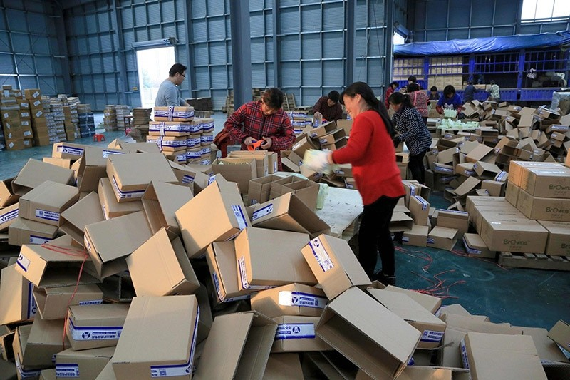Workers wrapping packages at a logistics center in Lianyungang, east China's Jiangsu province. China's courier services are planning ahead to cope with Singles' Day, yearly shopping boom day. Nov. 8, 2016. (AFP Photo)