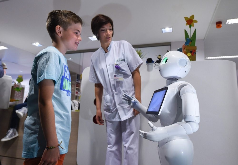 A young boy talks with the robot Pepper next to a nurse at the CHR Citadel hospital centers of Liege.