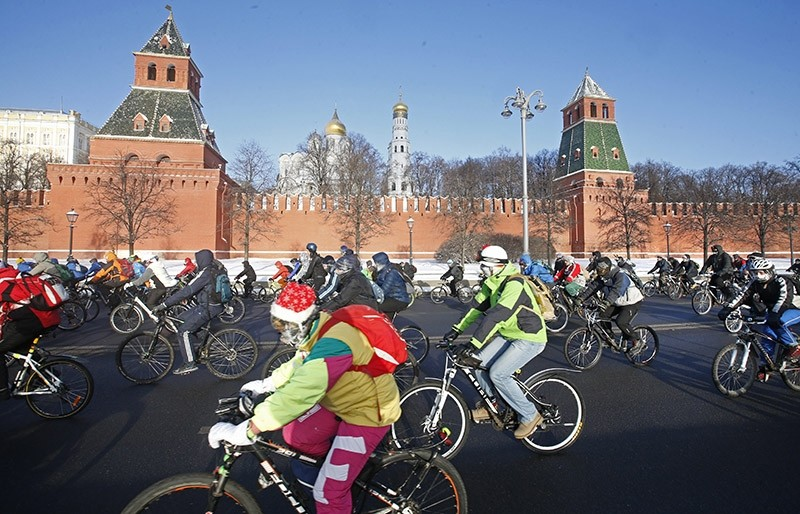Cyclists pass by the Kremlin as they are taking part in a winter bike parade in Moscow, Russia on January 2017. (EPA Photo)