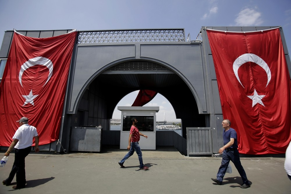 Men walking Galata Bridge where Turkish flag is displayed to protest the Gu00fclenists' failed coup attempt, Istanbul, Aug. 2.