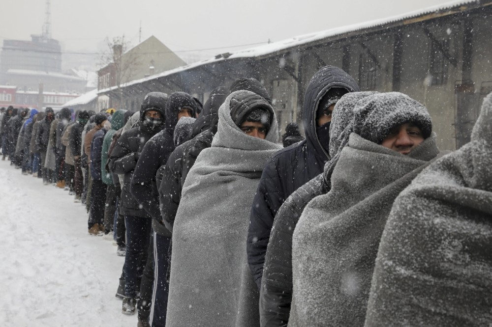 Refugees wait in line to receive a plate of free food during a snowfall outside a derelict customs warehouse in Belgrade, Serbia, Jan. 11.