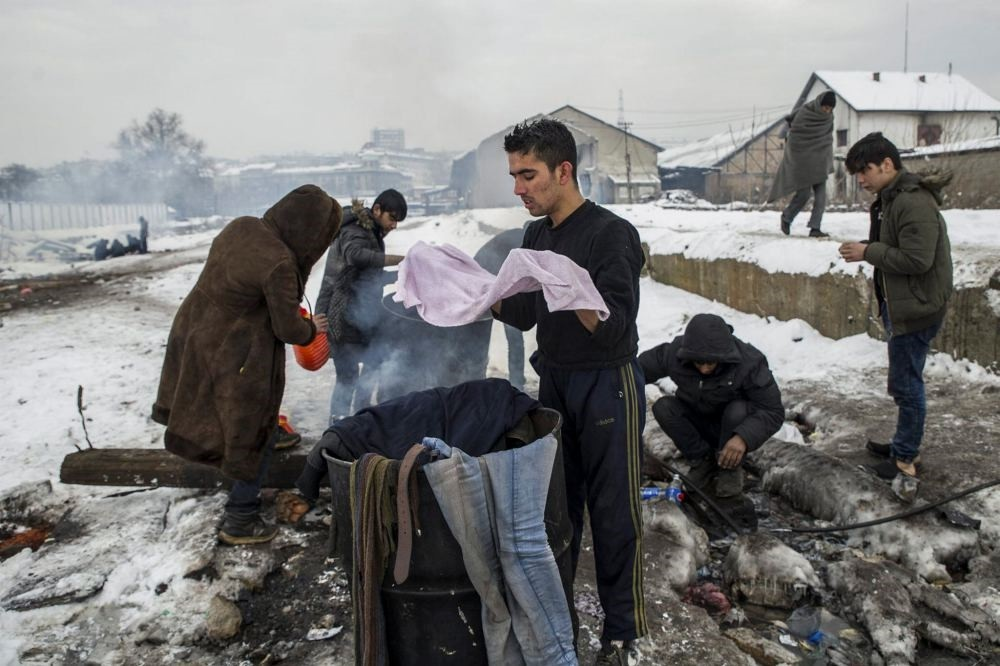 Refugees wash their clothes as they take a shower outside a derelict warehouse where they have taken shelter in Belgrade, Serbia on Jan. 12.