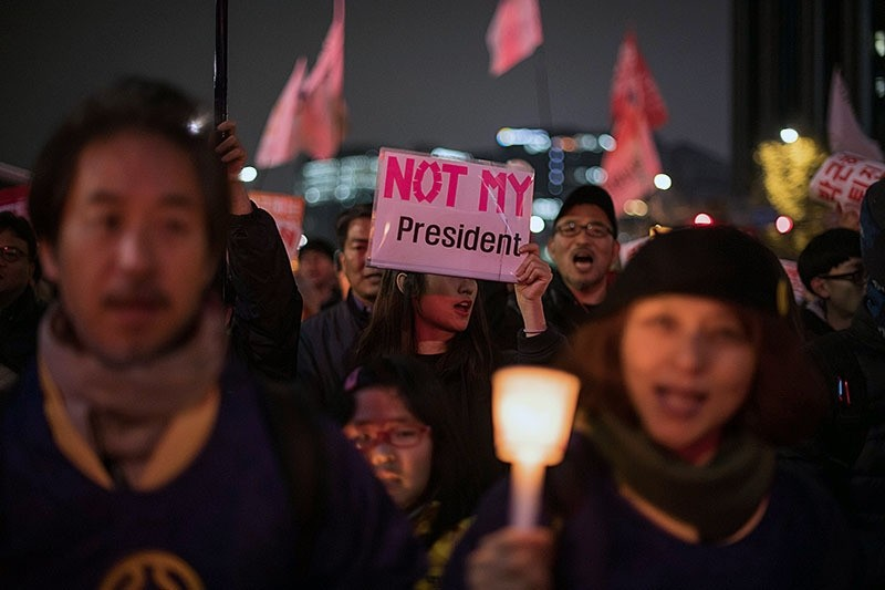 Demonstrators shout slogans and hold candles during an anti-government protest in central Seoul on November 19, 2016. (AFP Photo)