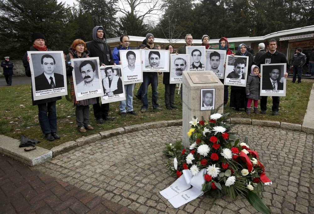 People carrying photos of NSU victims stand around a monument erected in memory of Halit Yozgat, one of the victims, in Germany's Kassel. Amnesty says ,institutional racism, led police to downplay racist motives behind the murders.