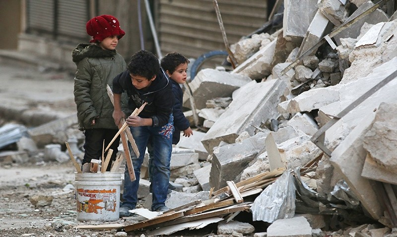 Children collect firewood amid damage and debris at a site hit yesterday by airstrikes in the rebel held al-Shaar neighbourhood of Aleppo, Syria November 17, 2016 (Reuters Photo)