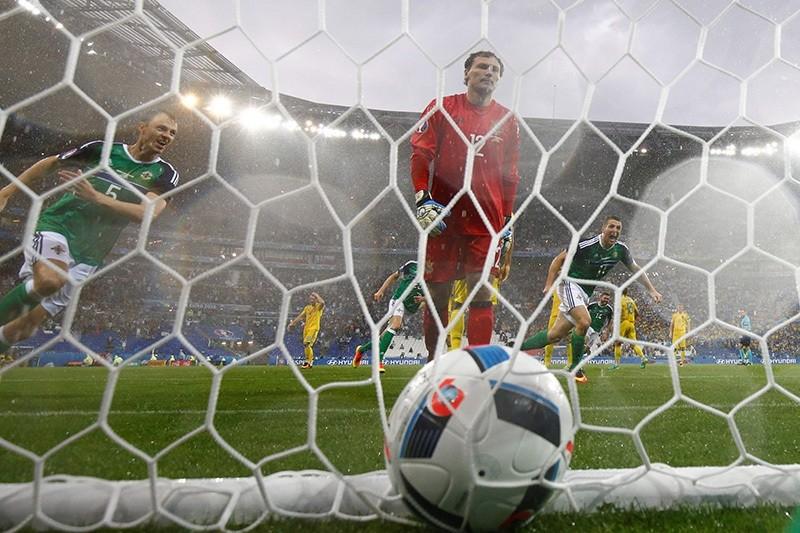 Northern Ireland's defender Jonny Evans (L) celebrates the opening goal scored by Northern Ireland's defender Gareth McAuley past Ukraine's goalkeeper Andriy Pyatov (AFP Photo)
