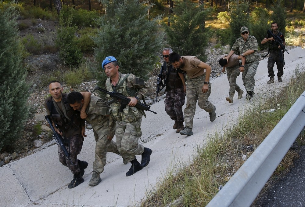 Soldiers and members of police's special forces unit accompany officers linked to the Gu00fclenist junta after their capture near the southwestern town of Marmaris last month.