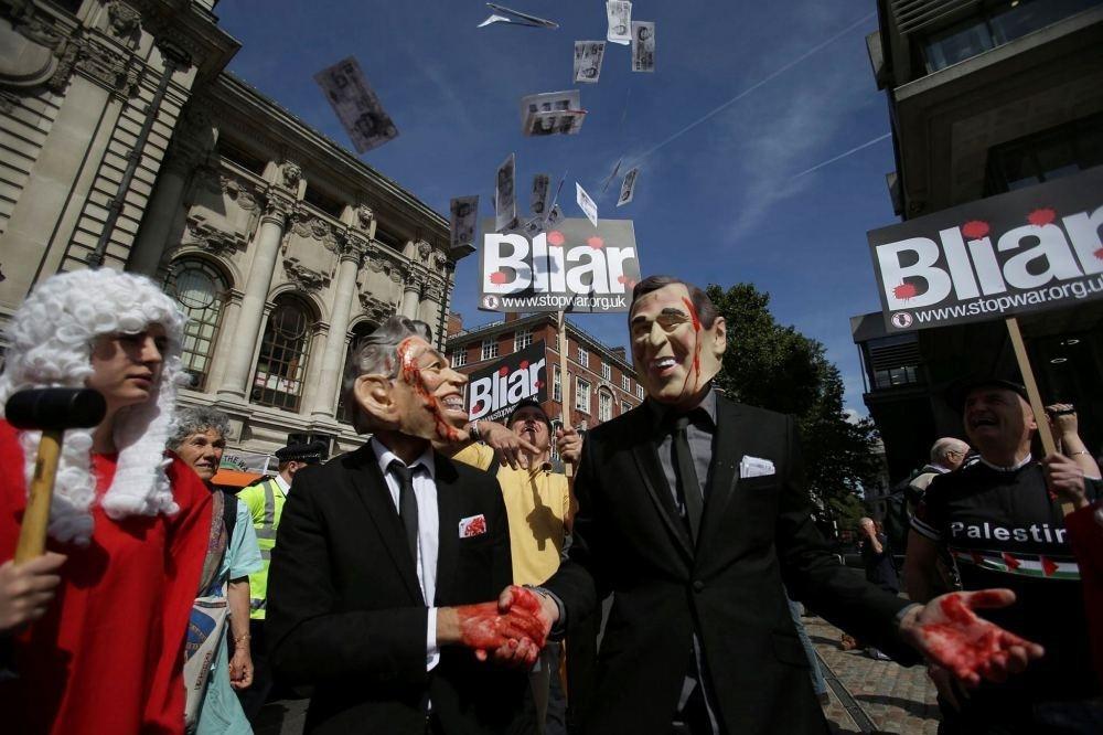 Demonstrators wearing masks depicting former British Prime Minister Tony Blair (L) and former U.S. President George W. Bush protest in Central London.