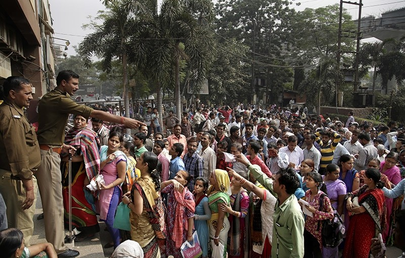 An Indian policeman asks people to wait patiently in queues to exchange or deposit discontinued currency notes, outside a bank in in New Delhi, India, Friday, Nov. 11, 2016. (AP Photo)