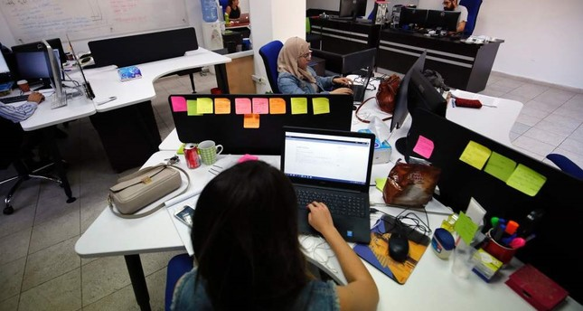 Palestinians work at the office of Red Crow, a startup that monitors security developments and sends real-time alerts and maps to clients, in Ramallah.