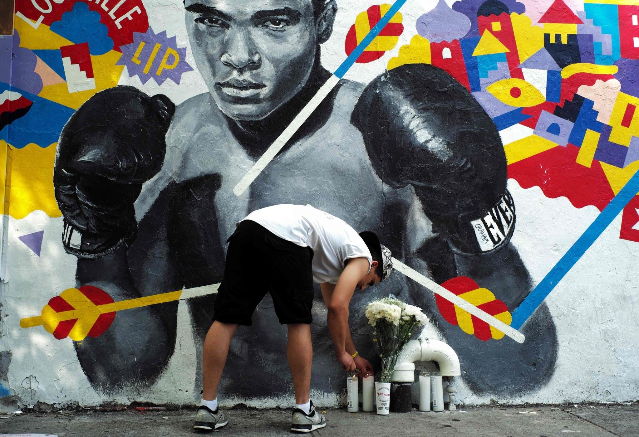 A man places a candle under a mural of the late boxer Muhammad Ali in New York on June 4, 2016 (AFP Photo)