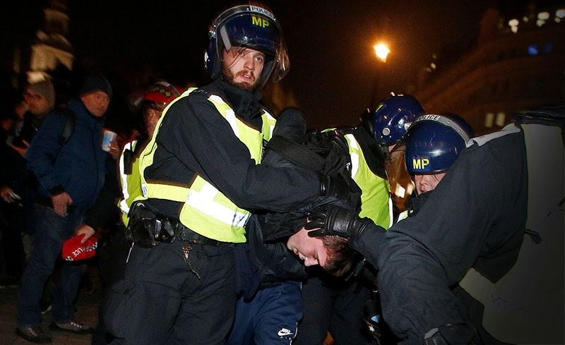 Police officers apprehend a protester during the ,Million Mask March, in London. (Reuters Photo)