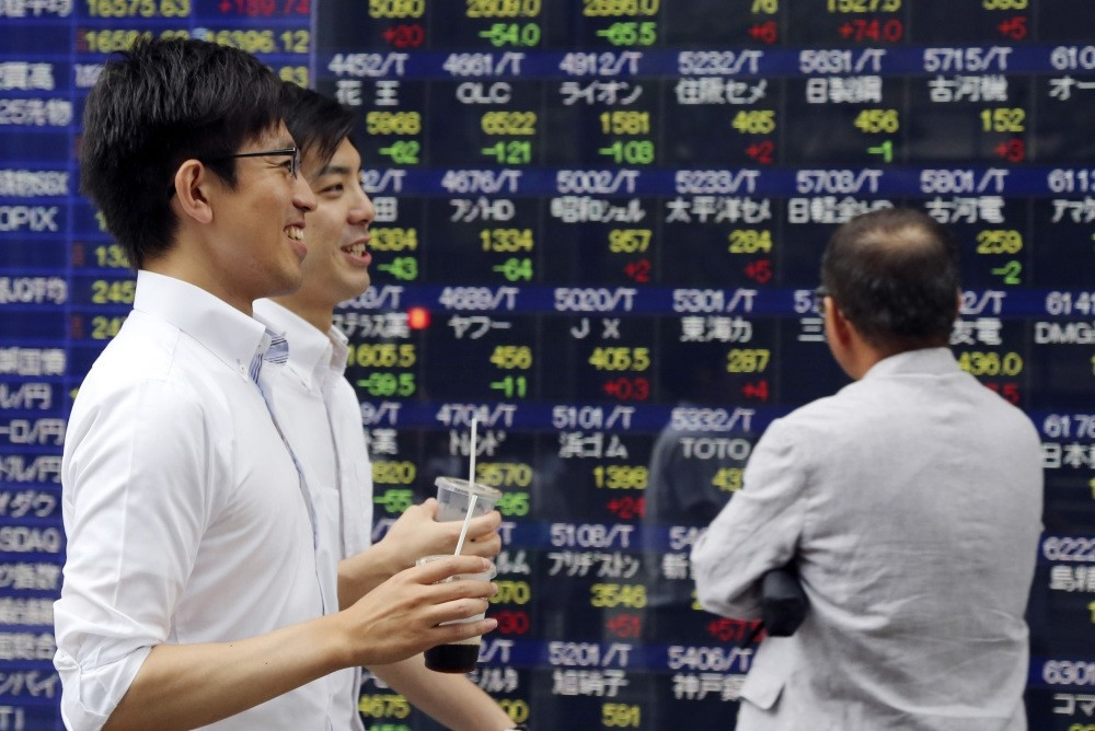 People walk by an electronic stock board of a securities firm in Tokyo, Friday, on July 15. Asian shares were higher Friday after China reported steady economic growth in the second quarter of the year.