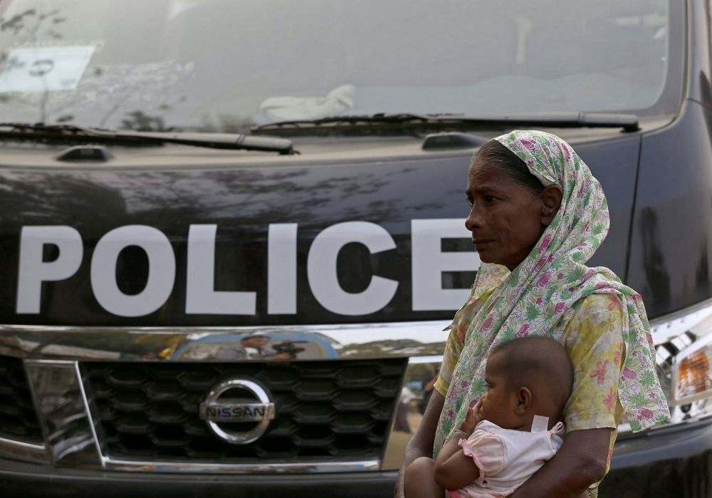 A Muslim woman carries her child as she stands near a police vehicle at the NgaKhuYa village near the Maungdaw town of Bangladesh-Myanmar border, Rakhine State, western Myanmar.