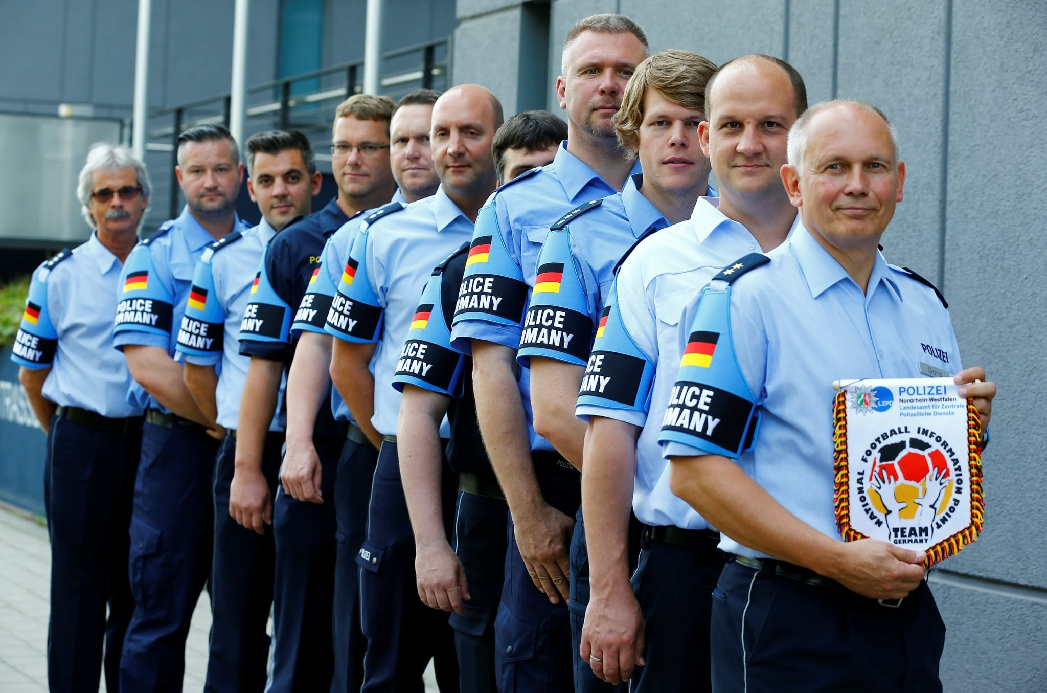 German police officers pose for an image with their armband reading ,Police Germany, at the North Rhine-Westphalian police headquarters in Duisburg, Germany, June 6, 2016.