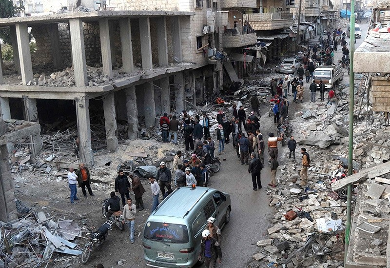 Syrian men and Civil Defense volunteers, also known as the White Helmets, inspect the damage following an air strike on the village of Maarat al-Numan, in the country's northern province of Idlib, on Dec. 4, 2016. (AFP Photo)