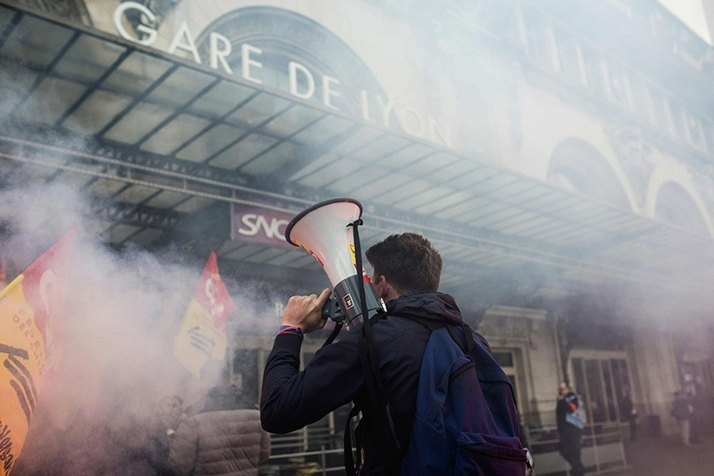 A protester holds a megaphone next to burning flares outside the Gare de Lyon in Paris on April 26, 2016, during a demonstration by railway workers of French state rail operator SNCF, as part of a strike to defend their work conditions. (AFP Photo)