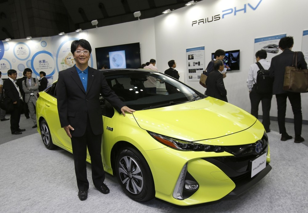 Chief Engineer Kouji Toyoshima poses with a Prius PHV at the Smart Community Japan exhibition in Tokyo.