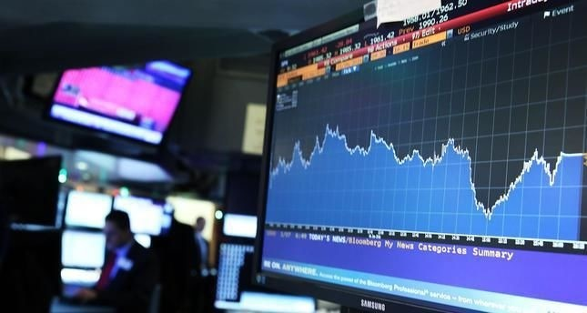 A screen shows the market movements as traders work on the floor of the New York