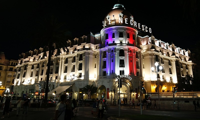This photo taken on July 17, 2016 on the Promenade des Anglais in Nice shows the Hotel Negresco illuminated in the colours of France's flag in tribute to the victims of the Bastille Day attack (AFP Photo)