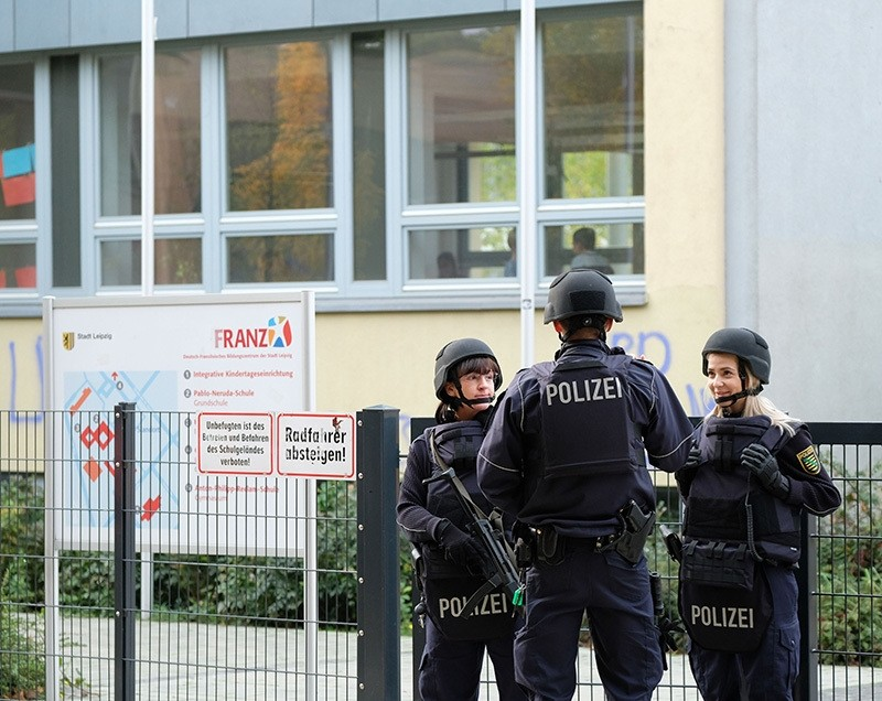 Police stand in front of the Reclam High School in Leipzig after the school received threats of violence by email, Germany, Oct. 17, 2016. (AP Photo)