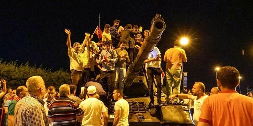 People stand on an abandoned tank and cheer after the failed coup attempt, in Istanbul.