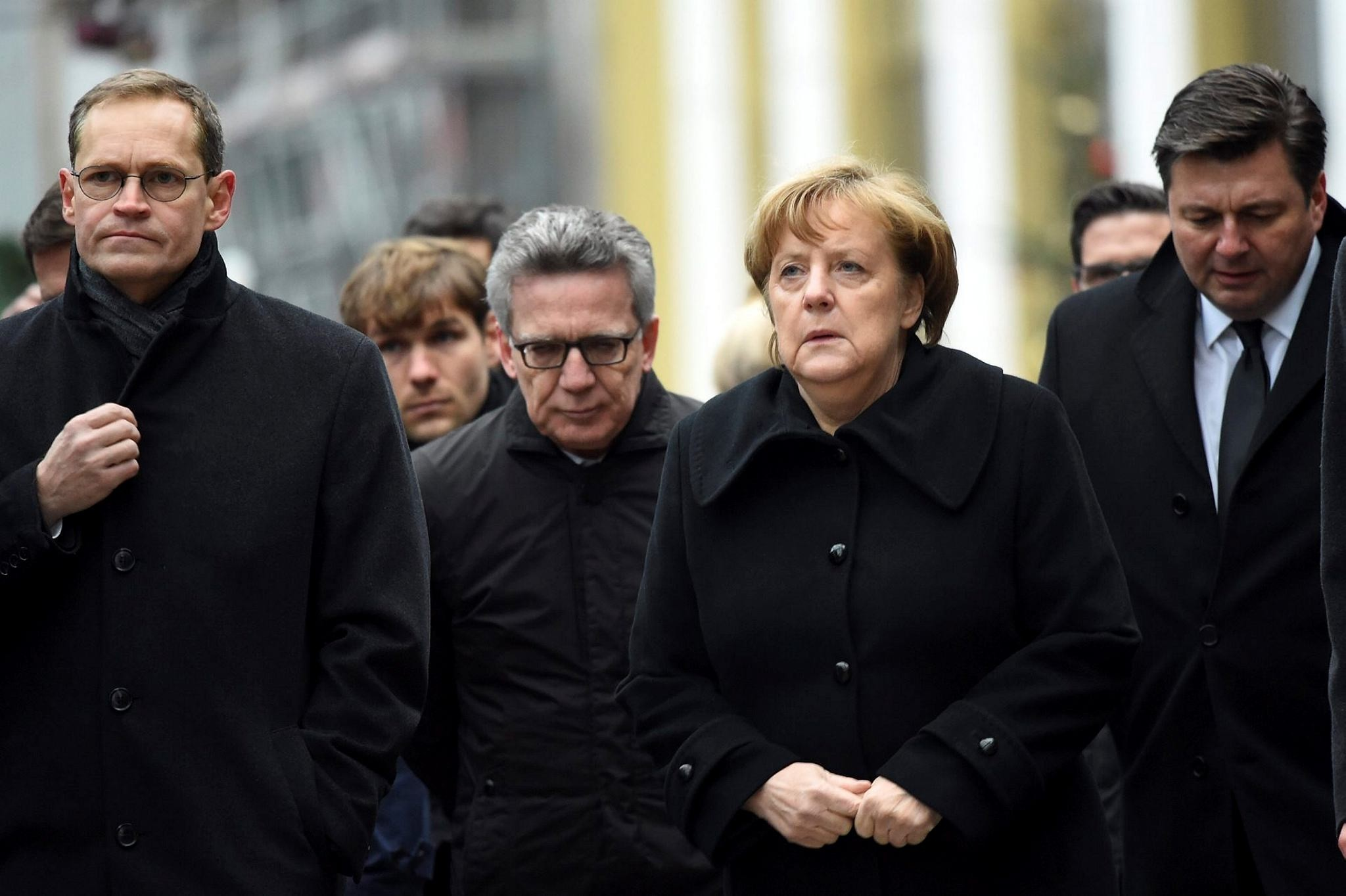 Berlin Mayor Michael Mueller (L), German Interior Minister Thomas de Maiziere (C) and German Chancellor Angela Merkel (R) visit the scene of an attack on a Christmas market in Berlin, Germany.