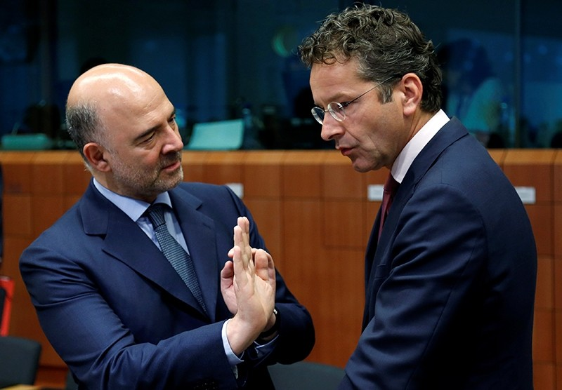 European Economic and Financial Affairs Commissioner Pierre Moscovici talks to Dutch Finance Minister and Eurogroup President Jeroen Dijsselbloem (R) during an euro zone finance ministers meeting. (REUTERS Photo)
