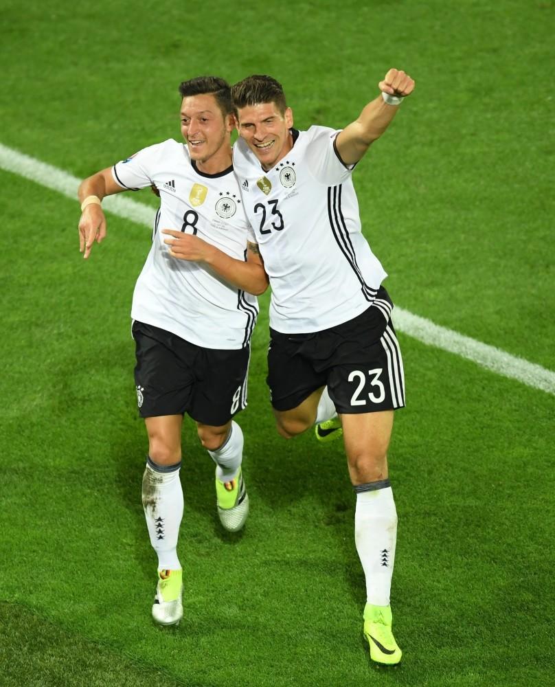 Mesut u00d6zil (L) and Mario Gomez celebrate goal against Italy.