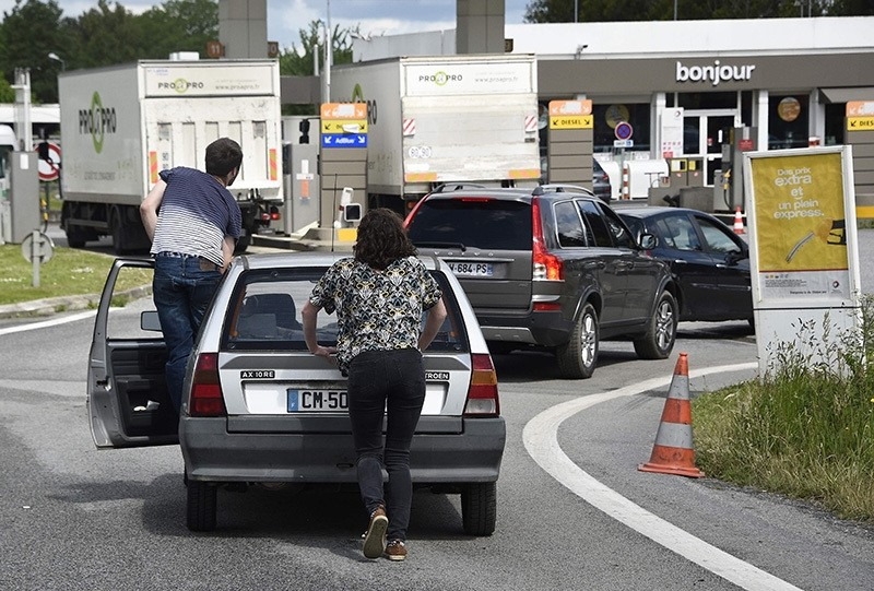 People push their car to save oil before refueling at a gas station following the blockades of oil depot (AFP photo)