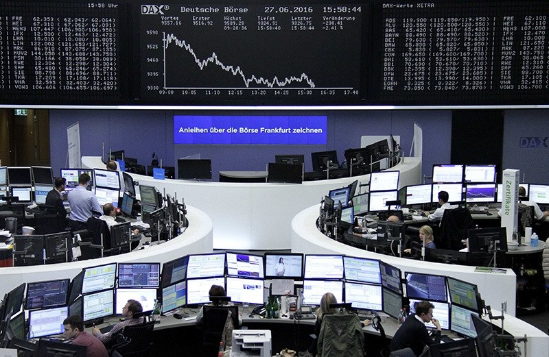 Traders work at their desks in front of the German share price index, DAX board, at the stock exchange in Frankfurt, Germany, June 27, 2016. (Reuters Photo)