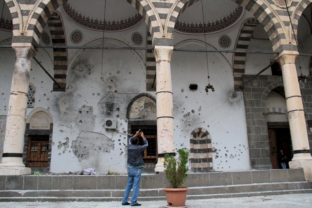 A man takes pictures of the damaged walls of a mosque in the Sur district of Turkeyu2019s southeastern Diyarbaku0131r province, Oct. 13, 2015.
