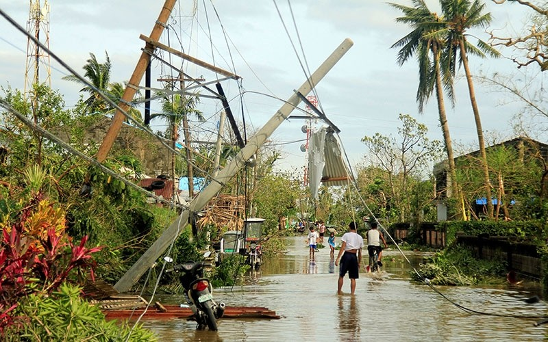 Residents walk past partially toppled electric posts after Typhoon Nock Ten hit Malinao, Albay in central Philippines December 26, 2016. (Reuters Photo)