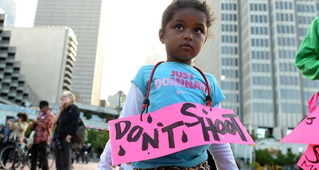 Nimani Darch-Walker, 3, wearing a sign that reads ,Don't Shoot,, looks on during a rally by the Black Lives Matter movement at Justin Herman Plaza in San Francisco, California on July 8, 2016. (AFP Photo)