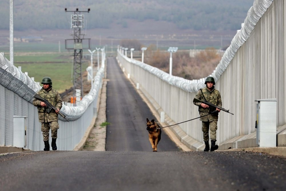 Troops patrol a completed part of the wall that stretches along the border.